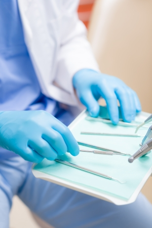 surgery table: Close-up of dentist hands prepare dental tools equipment surgery table