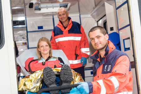 Paramedics helping woman on stretcher in ambulance smiling accident victim photo