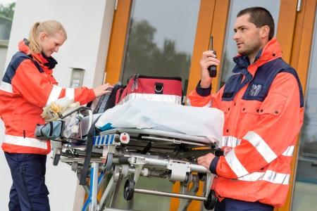 Emergency paramedics radio call ambulance house door visit doctor Stock Photo