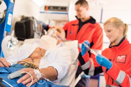 Zieke patiënt met paramedici in de ambulance behandeling hulp dringende werkzaamheden Stockfoto