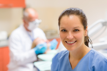 Female dental assistant smiling at stomatology office dentist with patient photo