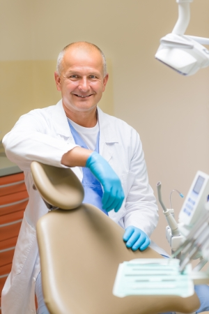 Portrait of mature smiling dentist sitting in modern dental surgery photo