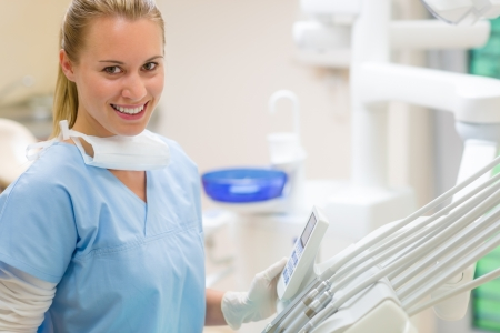 Female dentist with dental equipment at surgery smiling friendly staff photo