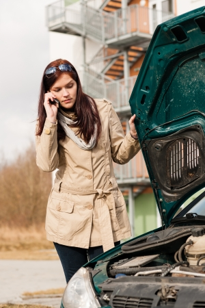 under pressure: Woman looking under car hood on phone breakdown accident problem Stock Photo
