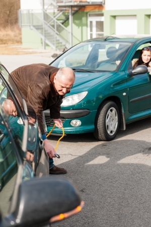 driving conditions: Man helping woman with her broken car problem breakdown cable