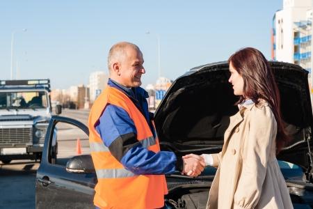 Vrouw begroeting monteur na haar autopech probleem man technicus Stockfoto