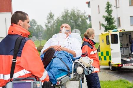 paciente en camilla: Paramédicos con el paciente sobre la camilla de emergencias hombre mujer ambulancia ayuda