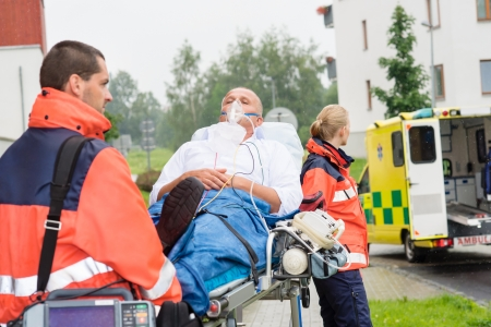 intubation: Paramedics with patient on emergency stretcher ambulance aid woman man