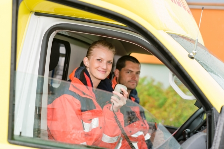 emergency call: Emergency paramedic in ambulance car talk radio smiling confident