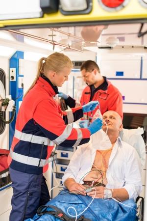 paciente en camilla: Paramédicos poner oxígeno máscara en ambulancia de emergencia enfermo paciente