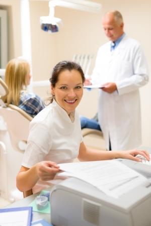 documentation: Dental assistant smiling woman prepare patient documentation stomatology clinic
