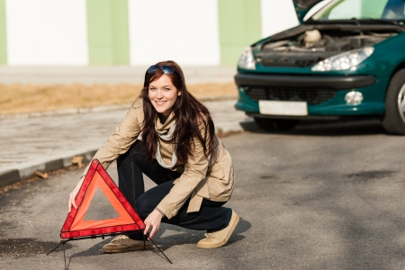 Woman putting warning triangle on the road car breakdown sign photo