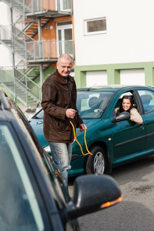 Man helping woman with her broken car problem breakdown cable photo
