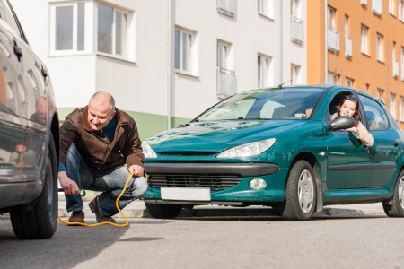 Mature man helping woman with her car breakdown broken problem photo