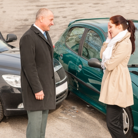 crash car: Man and woman talking after car crash sad guilt problem Stock Photo