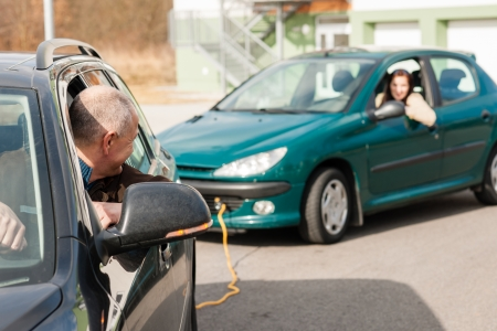 Man helping woman by pulling her car problem breakdown cable photo