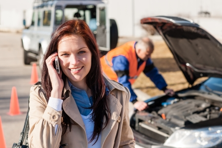 emergency call: Woman talking on cellphone after car breakdown trouble problem mechanic Stock Photo