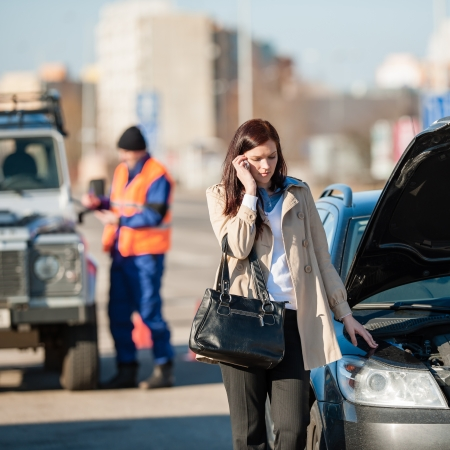 irritating: Woman on the phone after car crash breakdown talking upset