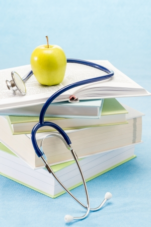 medical education: Medical books, apple and stethoscope healthy lifestyle medical research