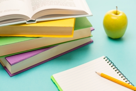 student desk: Pencil on notepad with school books and apple on student desk