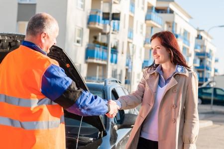 Woman greeting mechanic after her car breakdown problem man technician