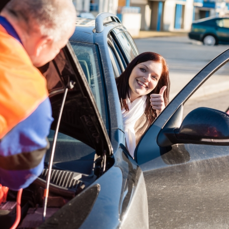 car trouble: Mechanic fixing car happy woman thumb up  breakdown problem Stock Photo