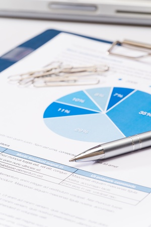graficas de pastel: Business pluma de plata sobre cartas de papel de oficina en primer plano