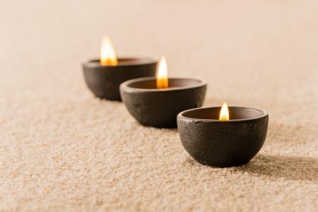 Balnéothérapie trois bougies sur le sable encore la nature Banque d'images