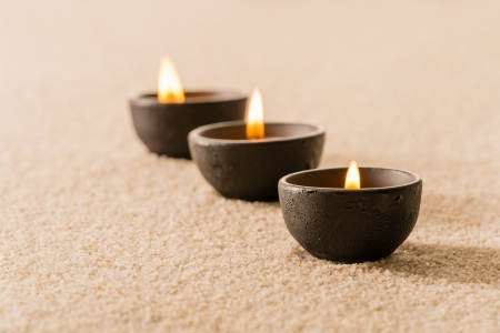 spa therapy: Spa therapy three candles on sand still nature Stock Photo
