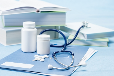 Doctor accessories and medications on blue background