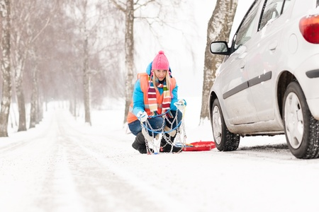 winter tyre: Woman with tire chains car snow breakdown smiling fixing winter Stock Photo