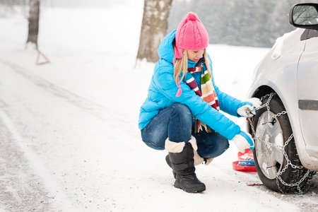 human chain: Woman putting winter tire chains on car wheel snow breakdown