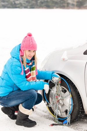 Snow tire chains winter car woman in trouble breakdown Stock Photo