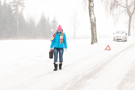 Woman carrying gas can snow car trouble winter breakdown walking photo