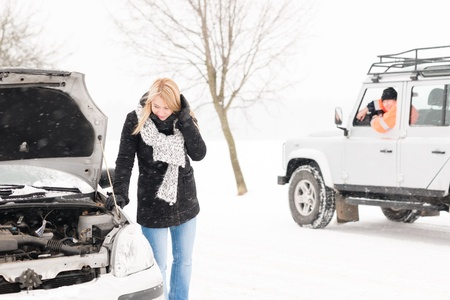 stuck: Woman looking under broken car hood snow trouble man assistance