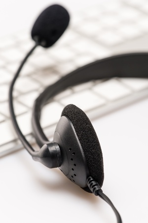 up service: Office headphones with microphone over white keyboard on desk Stock Photo