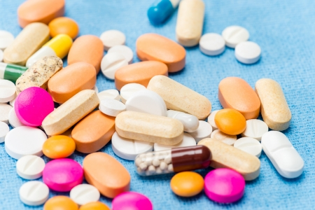 contraception: Color medicament pills spilled capsules on medical blue cloth