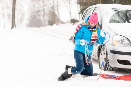Femme avec des pneus de voiture répartition des chaînes neige en hiver problématique jeune