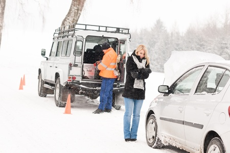 Mechanic helping woman with broken car snow assistance road winter photo