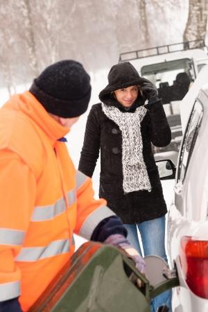 broken car: Man filling gas tank car breakdown woman winter snow assistance