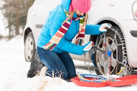 Femme mettant des chaînes sur la voiture de pneus neige d'hiver de fixation cassée Banque d'images