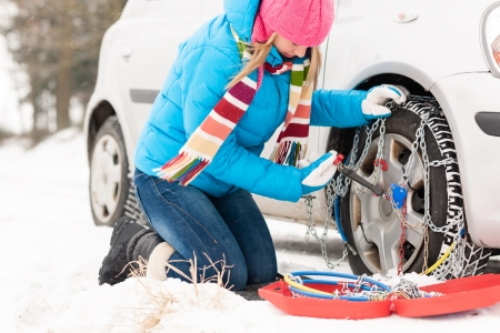 broken chain: Woman putting chains on car tires snow broken winter fixing