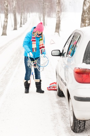 Woman snow standing with car tire chains holding winter broken Stock Photo - 15719429