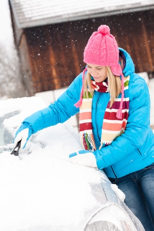 frustrating: Woman cleaning snow car hood with scraper winter wiping young