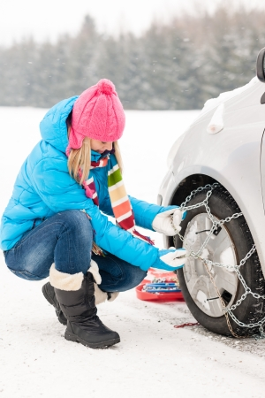 irritating: Woman putting winter tire chains on car wheel snow breakdown