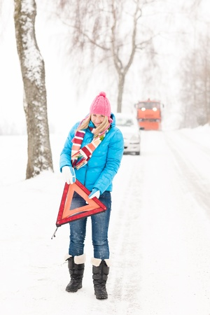 Woman with warning triangle car snow breakdown problem winter traffic photo