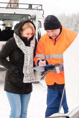 inquiry: Woman answering inquiry broken car snow mechanic assistance road winter Stock Photo