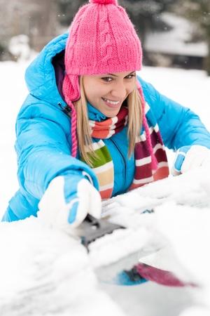 scraping: Woman brushing snow from car windscreen winter work scraper wiping Stock Photo