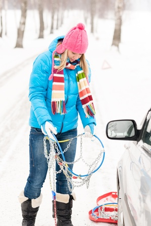 Woman snow standing with car tire chains holding winter broken Stock Photo - 15811703