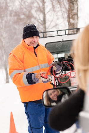 Man help woman broken car starting cables snow assistance winter photo